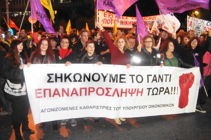 Sacked Greek Finance Ministry cleaners at the ERT rally. Their banner reads 'We have taken up the gauntlet –  Re-employment now'
