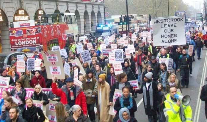 The mass march passes the Ritz Hotel – there is a growing gulf between the rich and poor in London, with working families being driven out of the capital