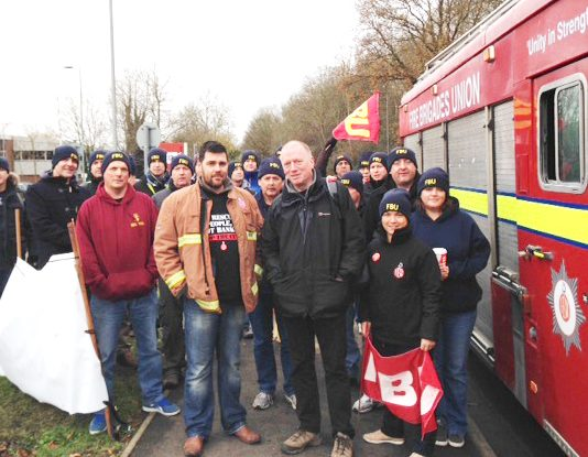 Victimised firefighter RICKY MATTHEWS (left centre) with FBU general secretary MATT WRACK at yesterday's march in Aylesbury
