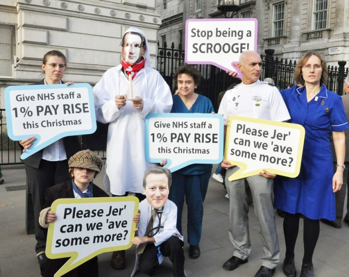 Health workers depicting Prime Minister Cameron and Health Secretary Hunt as Scrooges over the government's refusal to pay the 1% pay rise to all NHS workers
