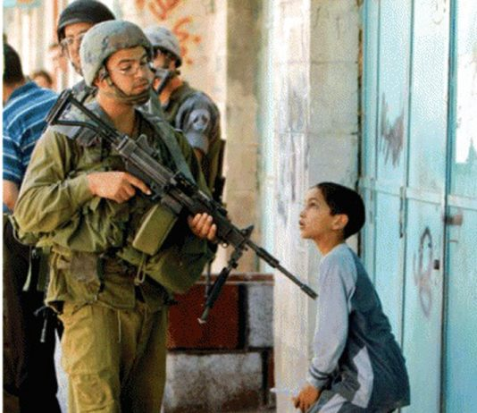 An Israeli soldier casually points his gun at a Palestinian boy