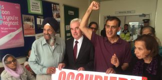 Labour MP for Hayes and Harlington John McDonnell holding the occupied banner with workers from Southall inside the maternity department