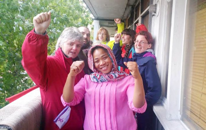 Aminata Sellu (centre) celebrates with supporters after successfully barring the way to bailiffs and the police