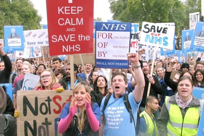 Some of the 20,000 Junior Doctors rallying in central London on Saturday display their defiance in the face of Health Secretary Hunt's attack on their contract