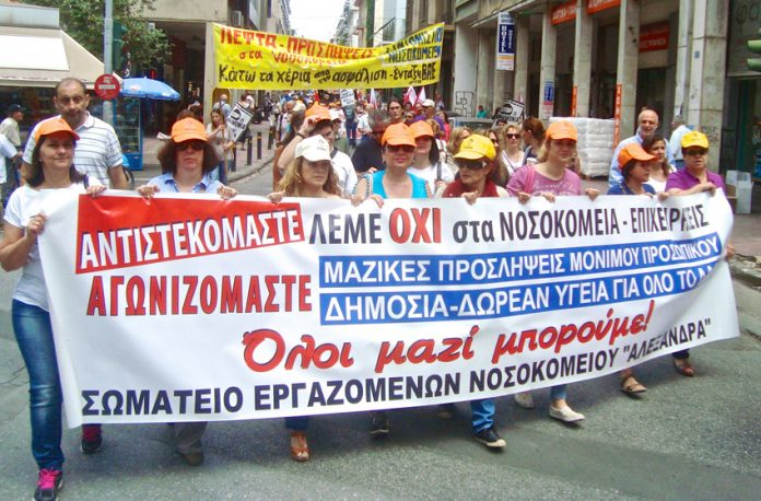 Greek hospital workers demanding free health care for all. Their banner declares 'All together we will win!'