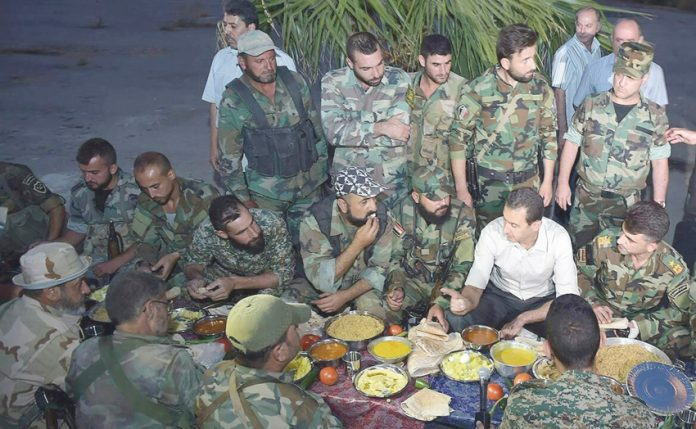 Syrian President Assad shares a meal with the troops of the Syrian army