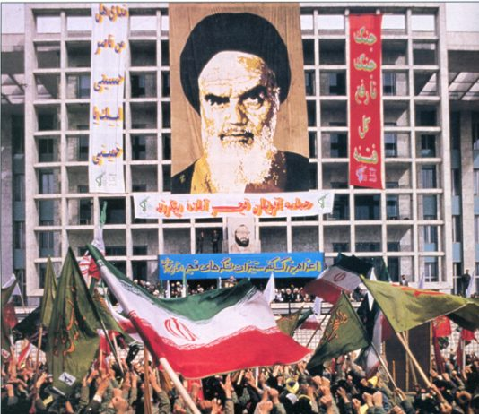 Portrait of Ayatollah Ruhollah Khomeini above a rally in Tehran marking the dispatch of forces to the front