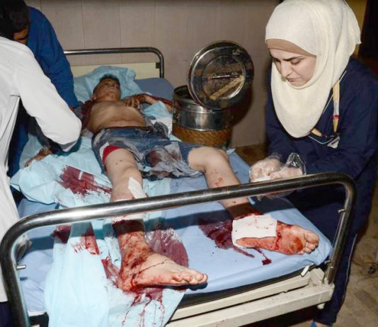 Syrian hospital workers treat a boy injured during a terrorist attack in Aleppo