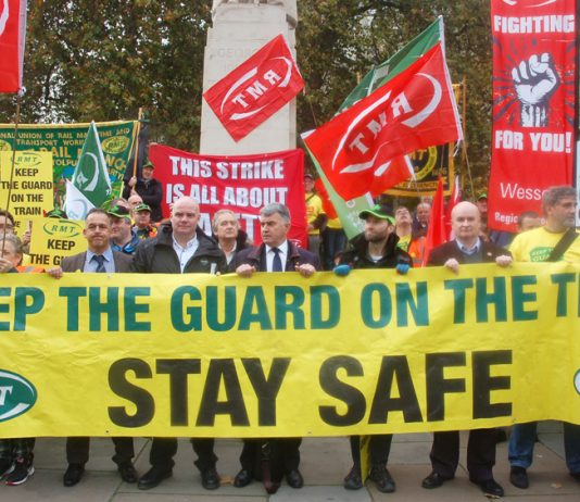 RMT president SEAN HOYLE, assistant general secretary STEVE HEDLEY and general secretary MICK CASH (all behind the banner from the front, left) on the union's 300-strong protest opposite parliament against driver-only trains