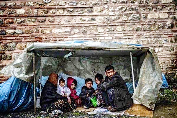 Refugee family – trying to keep alive from cold in a flimsy shelter. Photo credit: Panos Papanikolaou