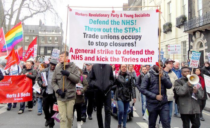 The Workers Revolutionary Party banner on the march to defend the NHS leading the fight to stop NHS privatisation and to smash the STP programme