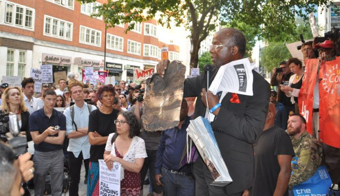 At a rally last Friday at the Department for Communities and Local Government a resident from north Kensington holds up a piece of charred cladding that had fallen from Grenfell Tower during the blaze