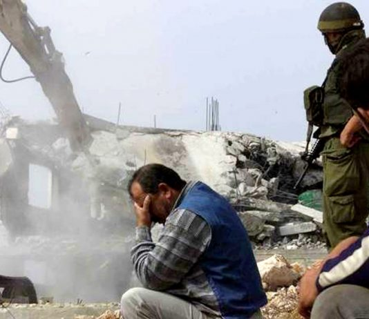 A Palestinian man in despair while his home is being demolished by the Israeli army as 'collective punishment'