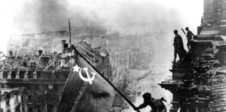 A Red Army soldier raises the Hammer and Sickle above the Reichstag, completing its liberation of Eastern Europe