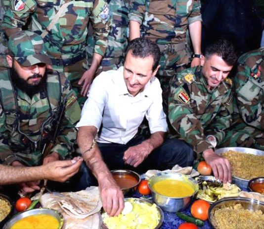 Syrian President Assad breaks his fast during Ramadan with Syrian troops