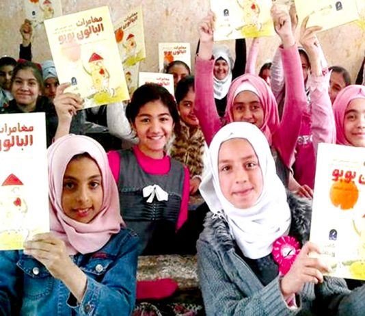 Young Iraqi girls hold copies of 'The Adventures of Booboo the Balloon'. They are now writing their own stories