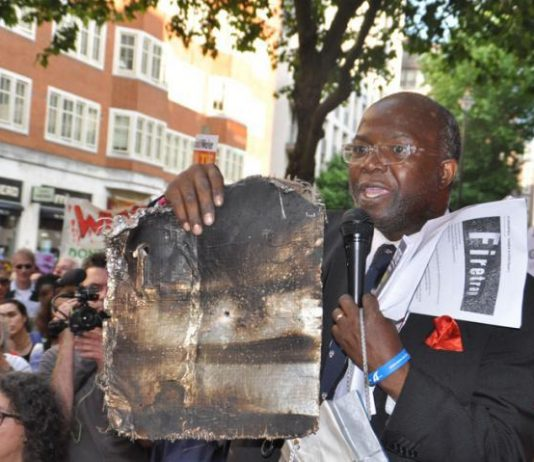 Grenfell resident holds up a piece of charred cladding which had fallen during the Grenfell Tower inferno