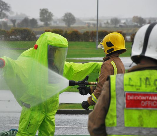 Firefighter in decontamination suit being hosed down