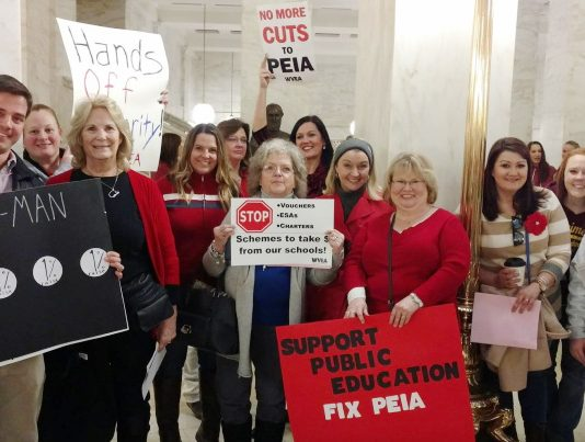 Striking teachers show their concern over the high rates they will have to pay to cover their health insurance