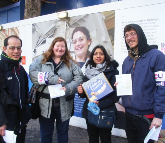 Striking university lecturers on the picket line at Imperial College are presented with a box of biscuits by a supporter