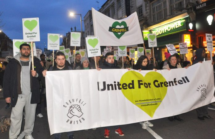 The front of the Silent March for Grenfell making its way down Kensington High Street