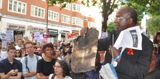 Resident of North Kensington holds a piece of the charred cladding from the Grenfell Tower inferno – building materials will still not be rigorously tested to see if they are flammable as the Tories have refused to rule out 'desktop assessments'