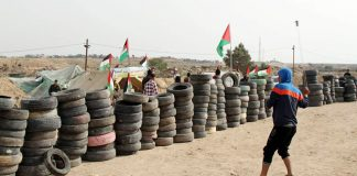 Palestinian youth prepare to set fire to piles of tyres on yesterday's massive 'Great March of Return' on the Gaza border