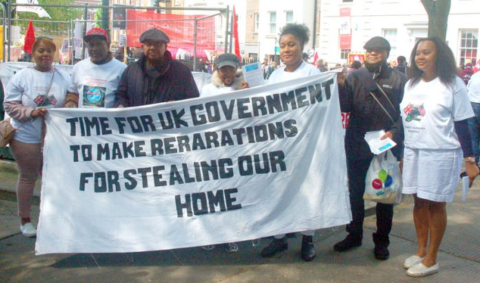 Chagos islanders at 2018 London May Day demonstration, Chagos Islanders with their banner demanding reparations from the government for the stealing of their homeland