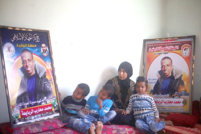 Muhammad al-Rabaia's mother and three sons sit beside posters honoring their slain father and son. Photo credit: Abed Zagout