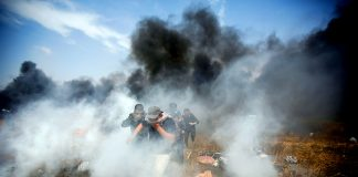 Palestinians emerge through clouds of teargas fired by Israeli troops at the Gaza border on the 6th Friday demonstration yesterday