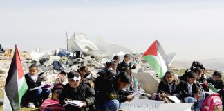 Palestinian children struggle to study in the open air after their school was bombed by Israeli forces