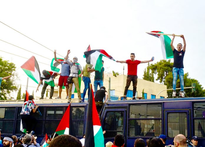 Palestinians in Athens climb on top of police buses and defiantly wave their flags