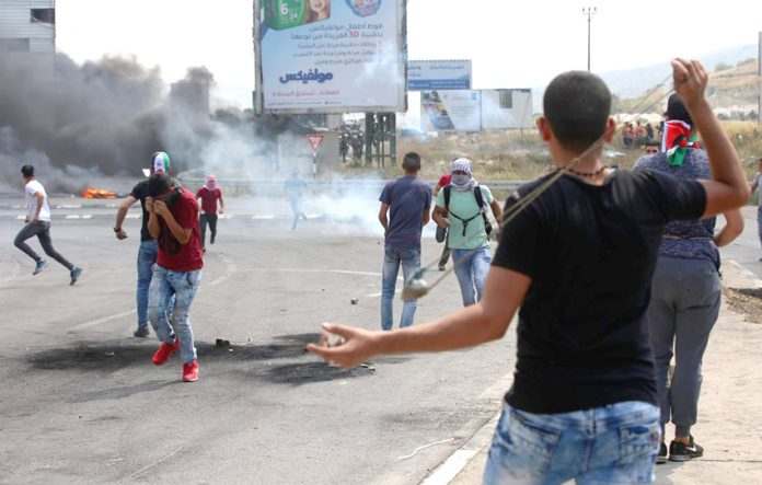 Palestinian youth clash with occupation forces at the Hawara checkpoint, south of Nablus city