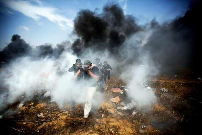 Young Palestinian demonstrators escaping the bombardment of tear gas and bullets from Israeli Defence Forces at the Gaza-Israel border fence
