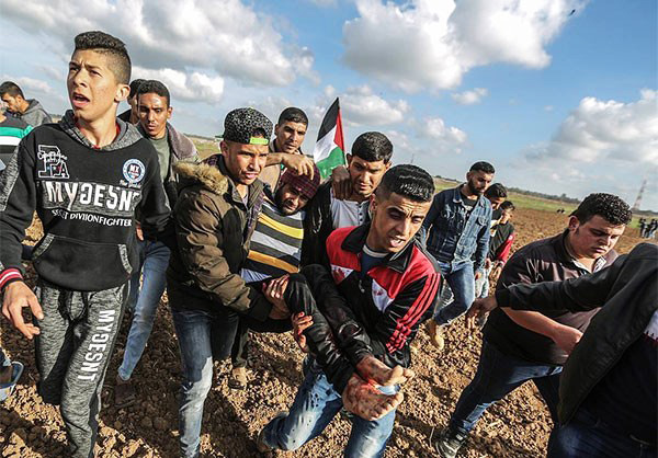Palestinian youth carry a man injured after being shot by Israeli forces on the Gaza border