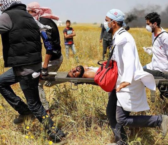 Palestinian wounded by Israeli sniper fire on the Gaza border is carried to safety