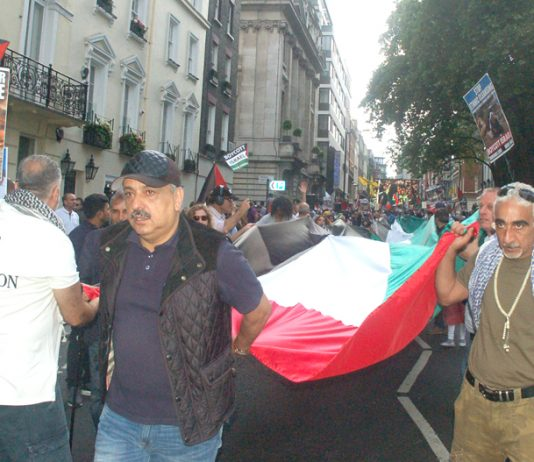 The march sets off, lead by a huge Palestinian flag, from outside the Saudi embassy in central London