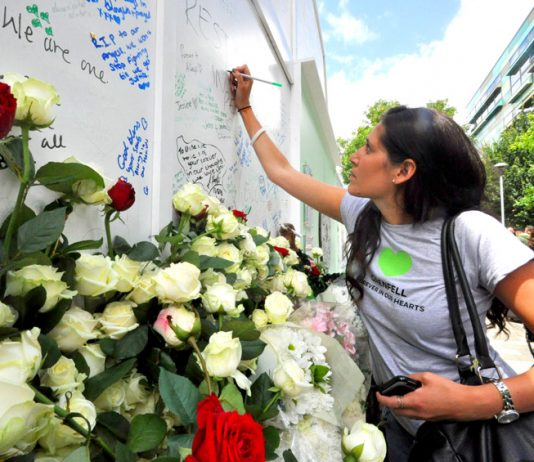 Writing tributes on the memorial at the base of Grenfell Tower yesterday