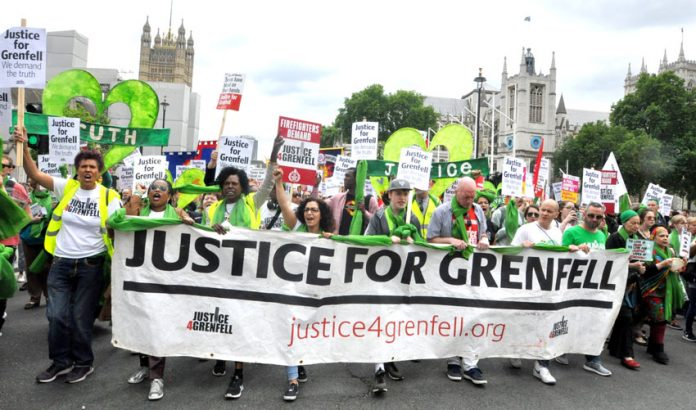 The front of Saturday's Grenfell march passes Parliament in London, England