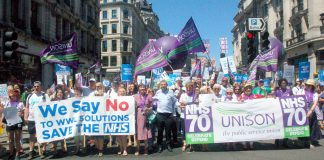 Unison members on the NHS 70th anniversary demonstration in London with (left) strikers from the Wrightington, Wigan & Leigh hospital over plans to transfer their jobs to a private company