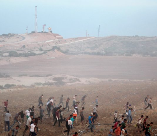 Palestinians on the Great March of Return on the Gaza border with Israel protest under the shadow of Israeli military observation posts and spy towers – farmers have now been fired on from these posts