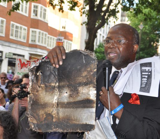A local resident holds up the charred remains of Grenfell Tower cladding – 468 buildings across the UK are clad in the same flammable aluminium composite – the Tories refuse to ban it