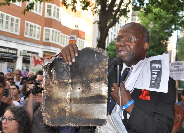 A local resident holds up charred remains of Grenfell Tower cladding – 468 buildings across the UK are clad in the same flammable aluminium composite – the Tories refuse to ban it