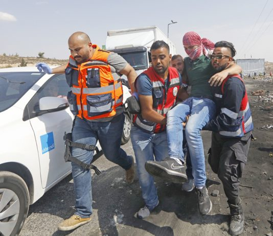 Medics help a Palestinian student on a protest against Israel's racist Nation State law after he was shot by Israeli troops