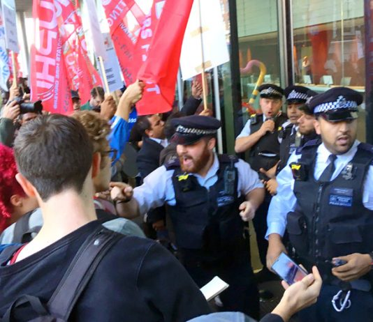 Police outside the Uber HQ desperate to stop Uber drivers and their supporters from entering the building