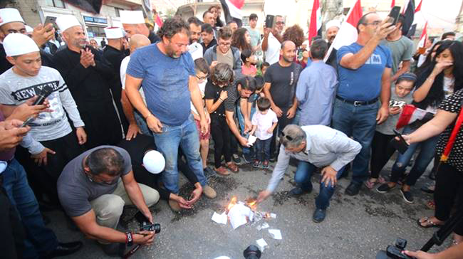 Syrians in the occupied Golan Heights burn ballot papers declaring the election void due to the Israelis illegal occupation
