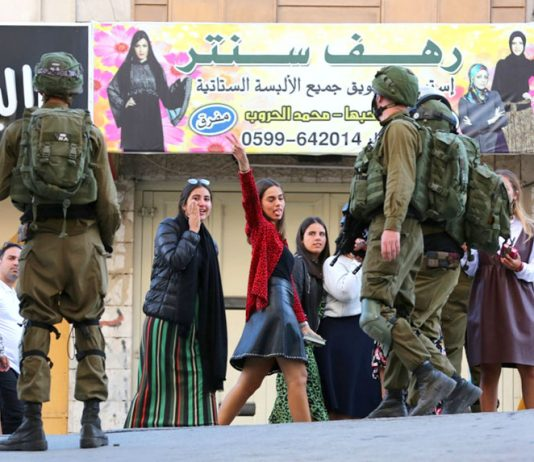 Palestinian girls in Hebron defy the occupying Israeli troops (above) after they had blocked off a road in the city on Friday (below) to allow access to Israeli settlers