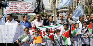 Children at the front of a protest in Ramallah against the cut in aid to UNRWA