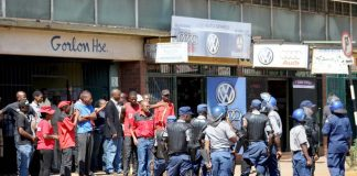 Riot police and workers clash outside the ZCTU offices after protests against Zimbabwean government tax hikes last October