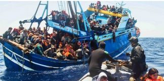 Refugees aboard an overloaded boat desperately trying to cross the Mediterranean